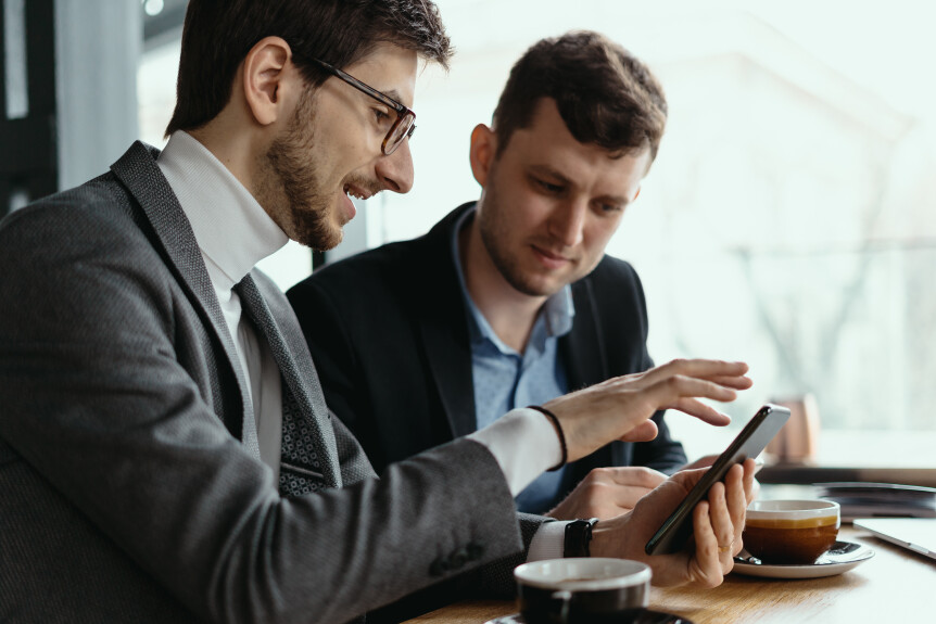 One-on-one meeting. Two young business people sitting at table in restaurant having a conversation using a phone and having a coffee. Businessman using a smartphone